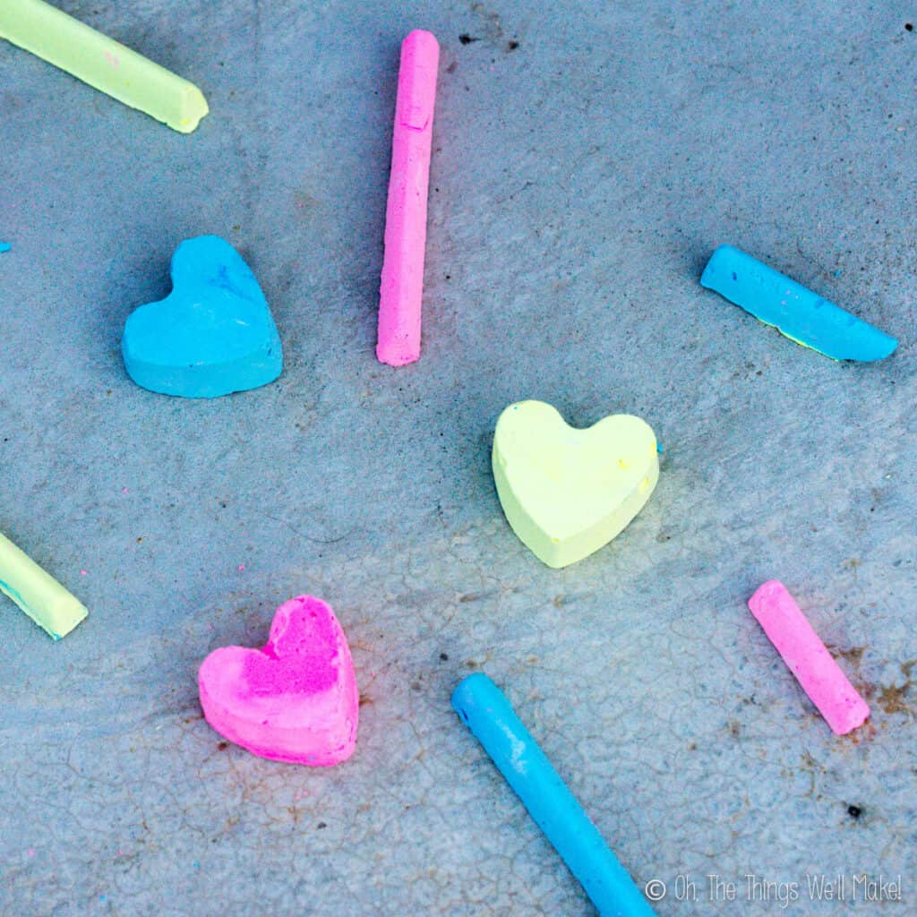 Overhead view of several pieces of homemade sidewalk chalk in three bright colors.
