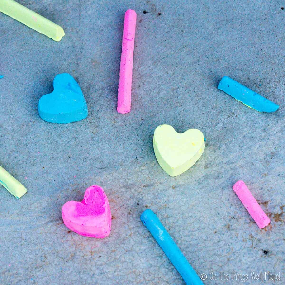 Overhead view of several pieces of homemade sidewalk chalk in three bright colors: pink, blue, and yellow.