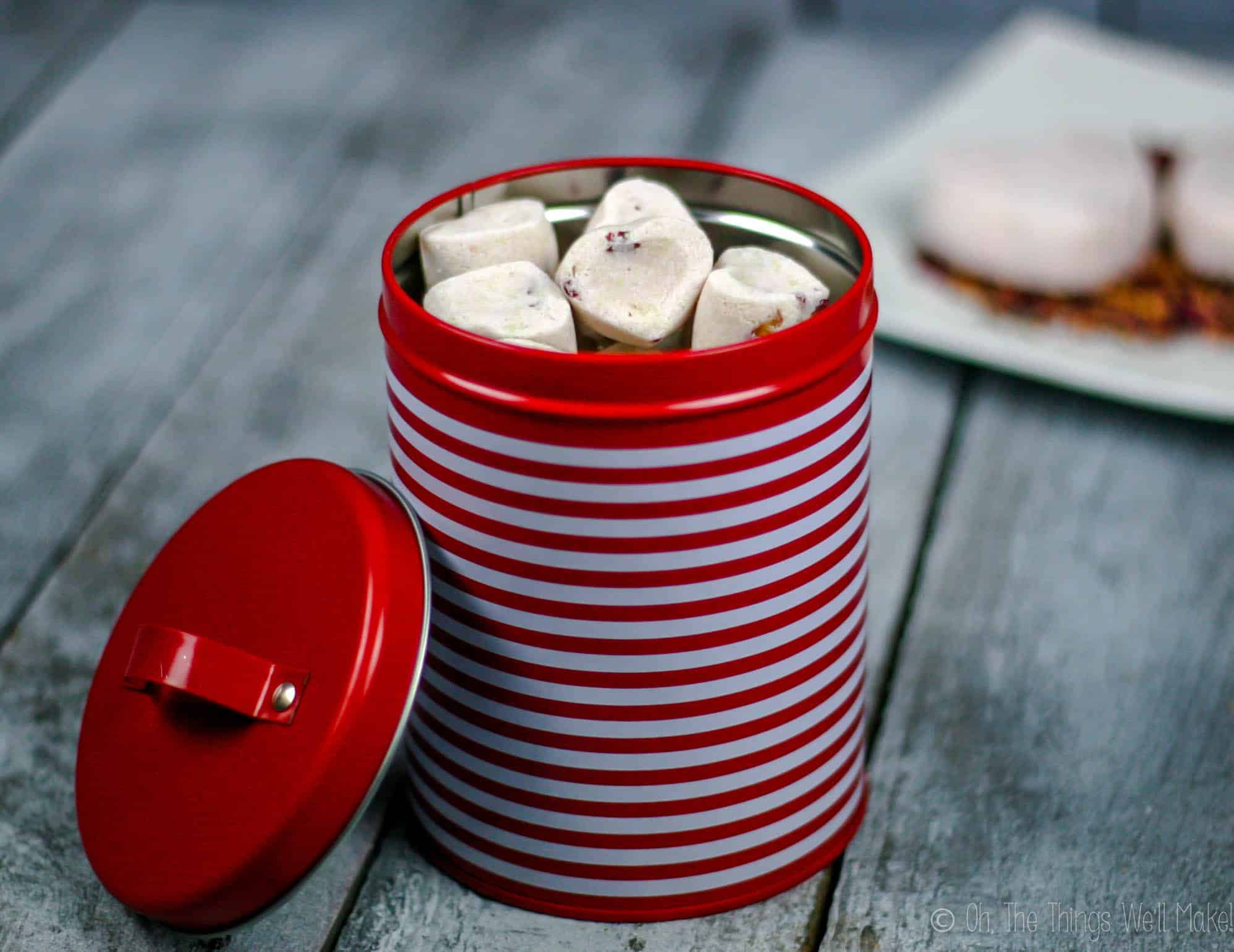 A red tin filled with small rose petal bath bombs. Behind it, tow larger bath bombs are on a plate with rose petals.