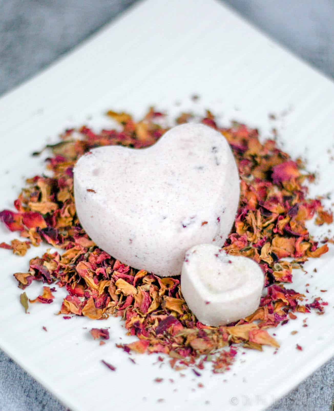 Two heart-shaped bath bombs on a plate with rose petals.