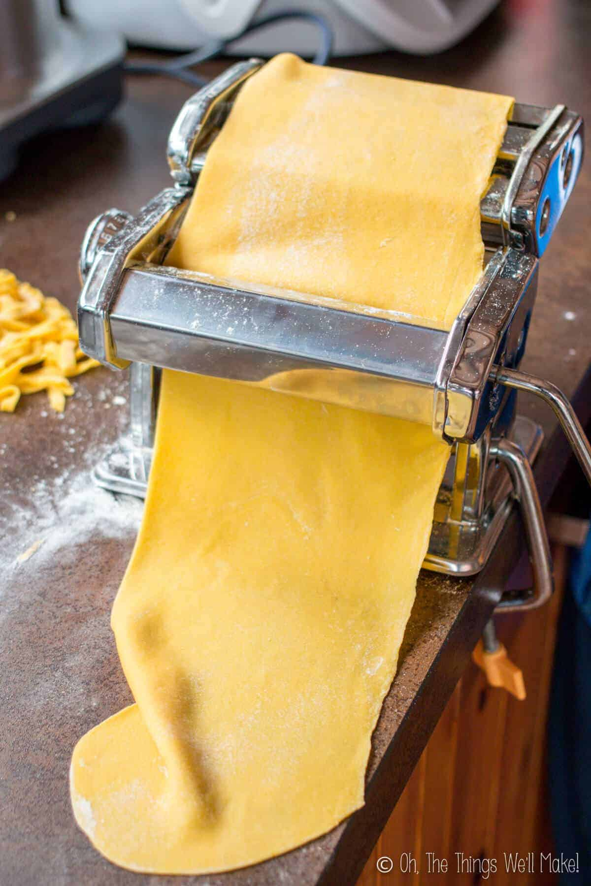 Running the pasta through a pasta maker to help flatten it out and make think sheets ready for cutting into fettuccine.