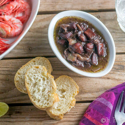 Calamares al vino tinto, or red wine braised squid, as seen from above served with bread and red prawns