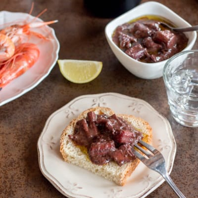 A plate of red wine braised squid on top of a slice of bread with a plate of shrimp, slice of lemon, and a bowl of squid in the background.