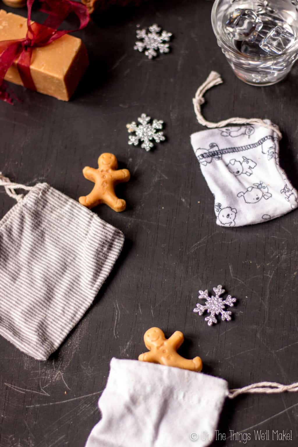 Three pouches laid on a black surface with some snowflake and gingerbread decor around. From top to bottom: white with dog print pouch, striped pouch,  and white pouch.