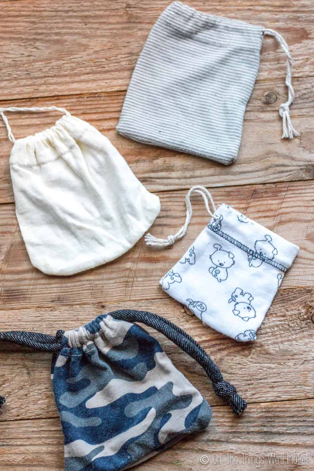 Four different drawstring pouches made form the sleeves of baby clothes, laid on a wood surface. From top to bottom: a grey striped pouch, a white one, a white with dog print, and a camouflage print pouch.