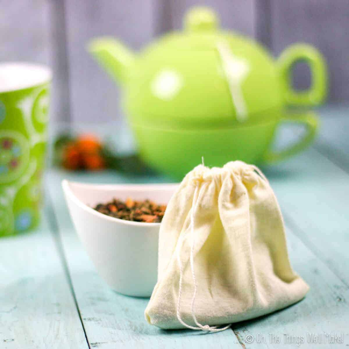 Closeup of a homemade cloth teabag with a small bowl behind it filled with a loose tea. In the background, there is a green teapot and a teacup.