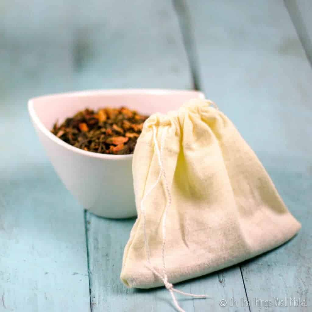 Closeup of a homemade cloth teabag with a small bowl behind it filled with a loose tea.