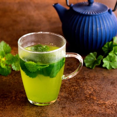 A clear glass full of freshly brewed green stinging nettle herbal tea, place in front of a blue cast iron teapot.