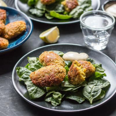 Several plates full of pieces of turmeric falafels placed on top of leafy greens with a dollop of sauce on the side.