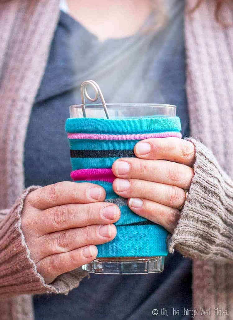 Closeup of hands holding a steamy cup of tea with a homemade coffee cozy over the cup.