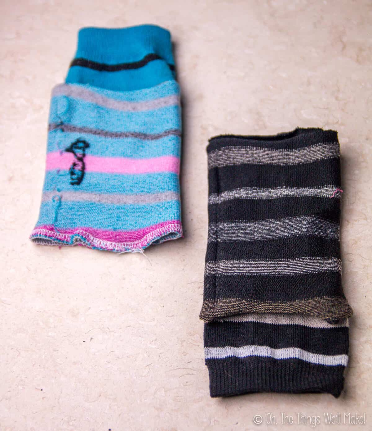 Two sock pieces, one striped blue and one black striped, put together with right sides facing in, ready to be sewn.