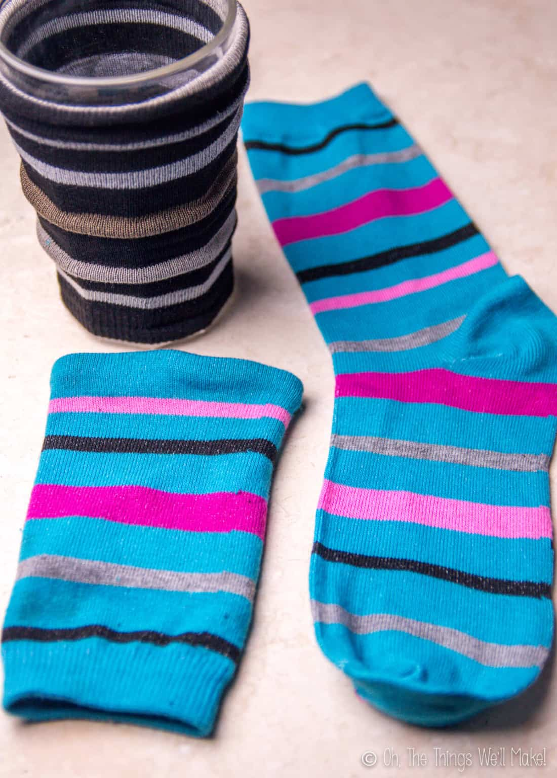 The finished black striped coffee cozy slipped over a glass with a finished blue striped coffee cozy laid down next to a striped blue sock.