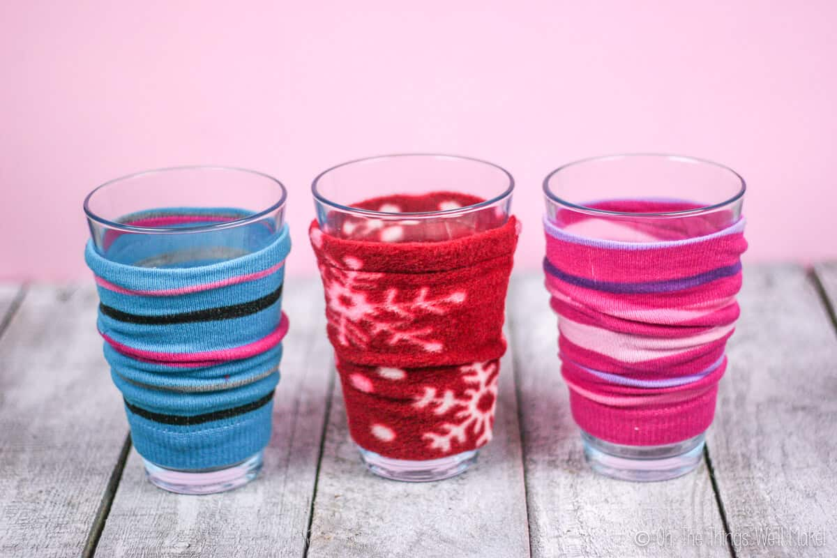 Three coffee cozies on glasses standing on a wood surface. The left one is a blue striped cozy made out of a sock, the middle one is a red polar fleece fabric cozy, and the right one is pink striped cozy made out of a sock.