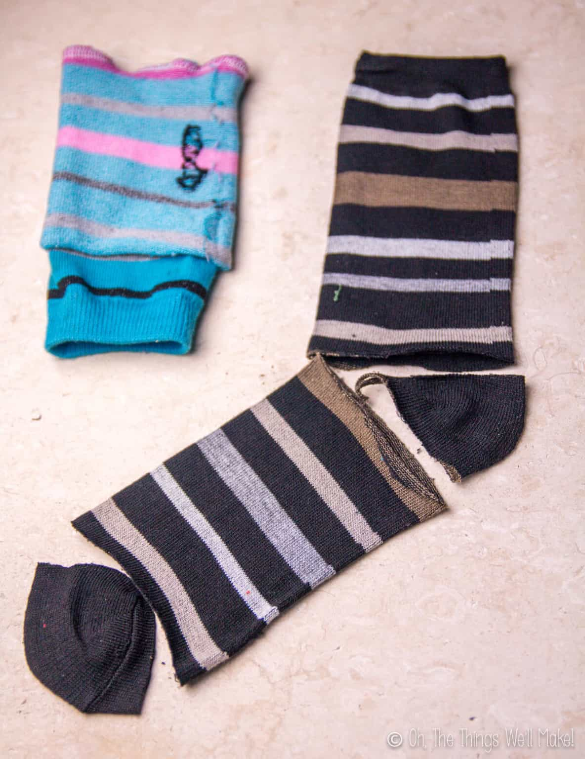 Top view of a black sock whose heel and toe areas have been cut out, and a blue sock that has been cut out and laid inside out.