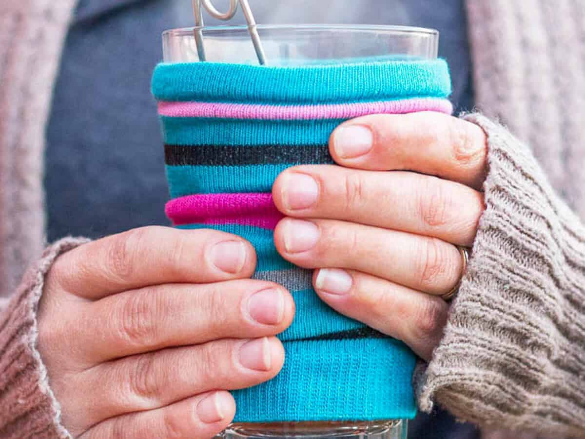 A closeup of a woman's hands holding a hot glass of coffee covered in a bright striped blue and purple cozy made out of a sock.