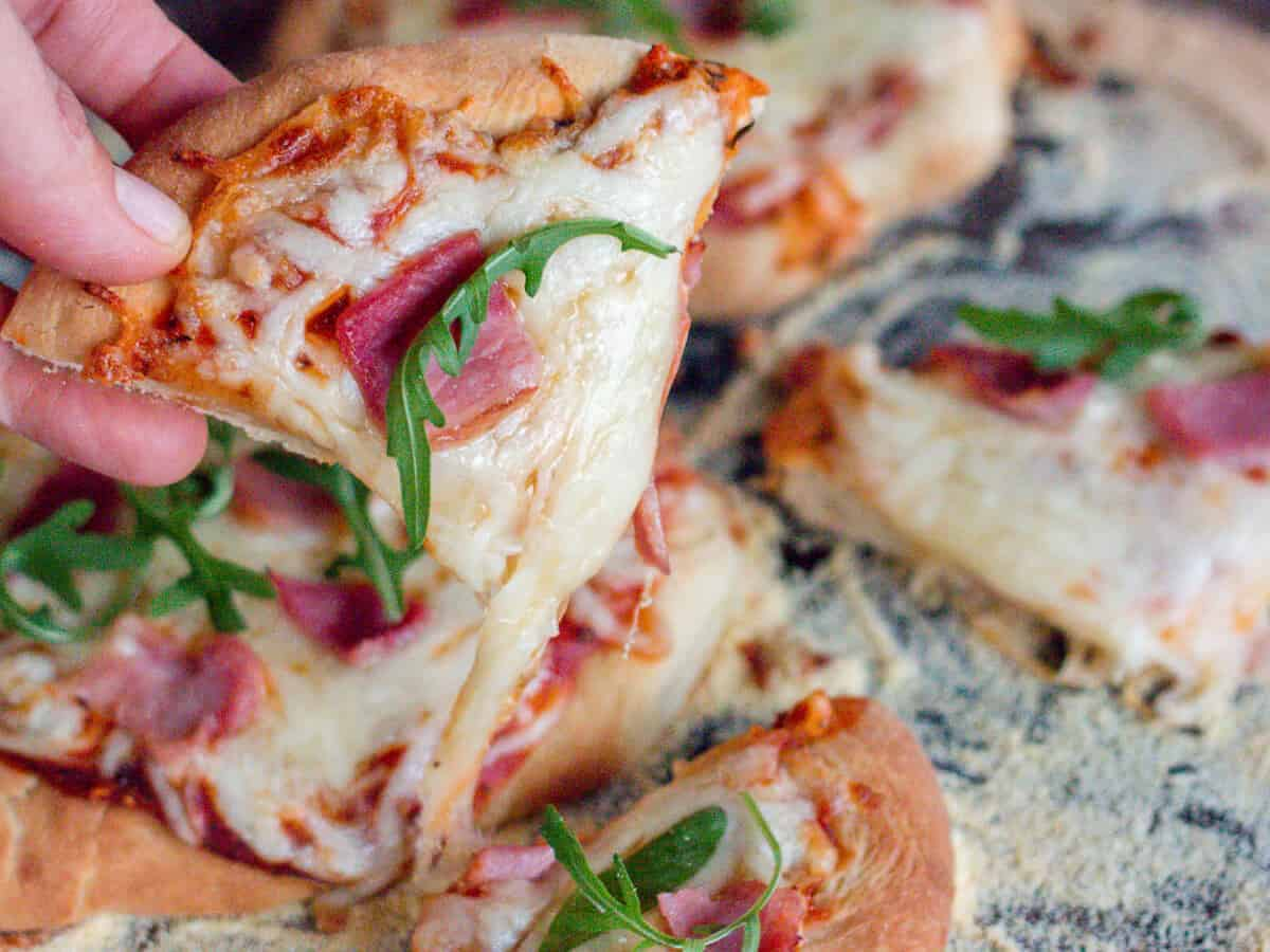 Close-up of a slice of mini pizza made out of homemade pizza dough. Pizza is filled with cheese, piece of meat and leafy greens.