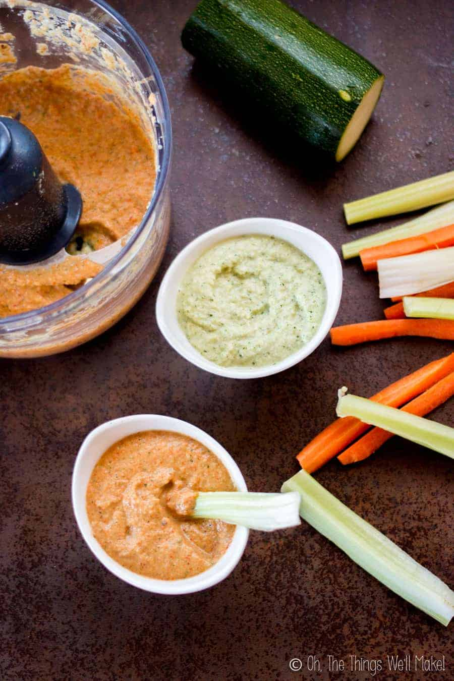 Dipping celery into a roasted red pepper zucchini hummus by a food processor with more zucchini hummus