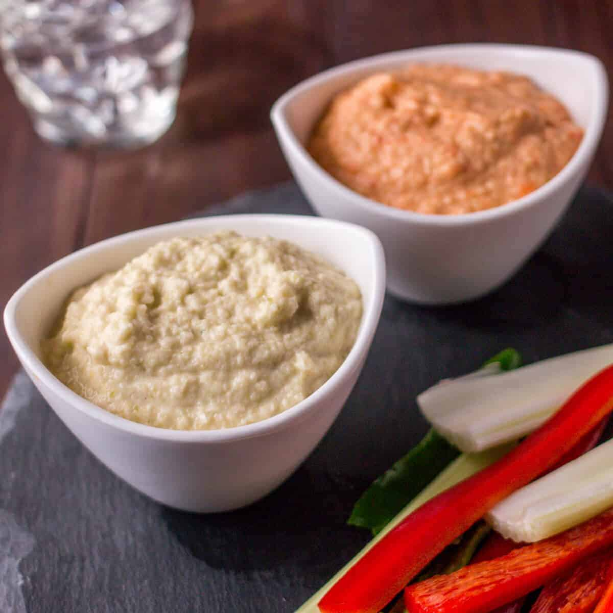 2 bowls of zucchini hummus, one cream colored and the other orange colored because it's made with roasted red peppers. They're surrounded by cut raw veggies.