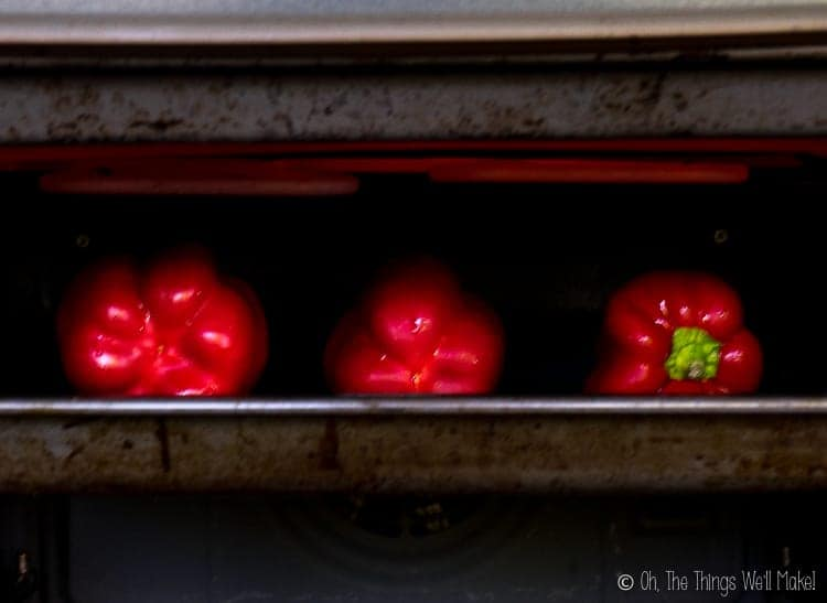 3 red peppers on a baking sheet under a broiler