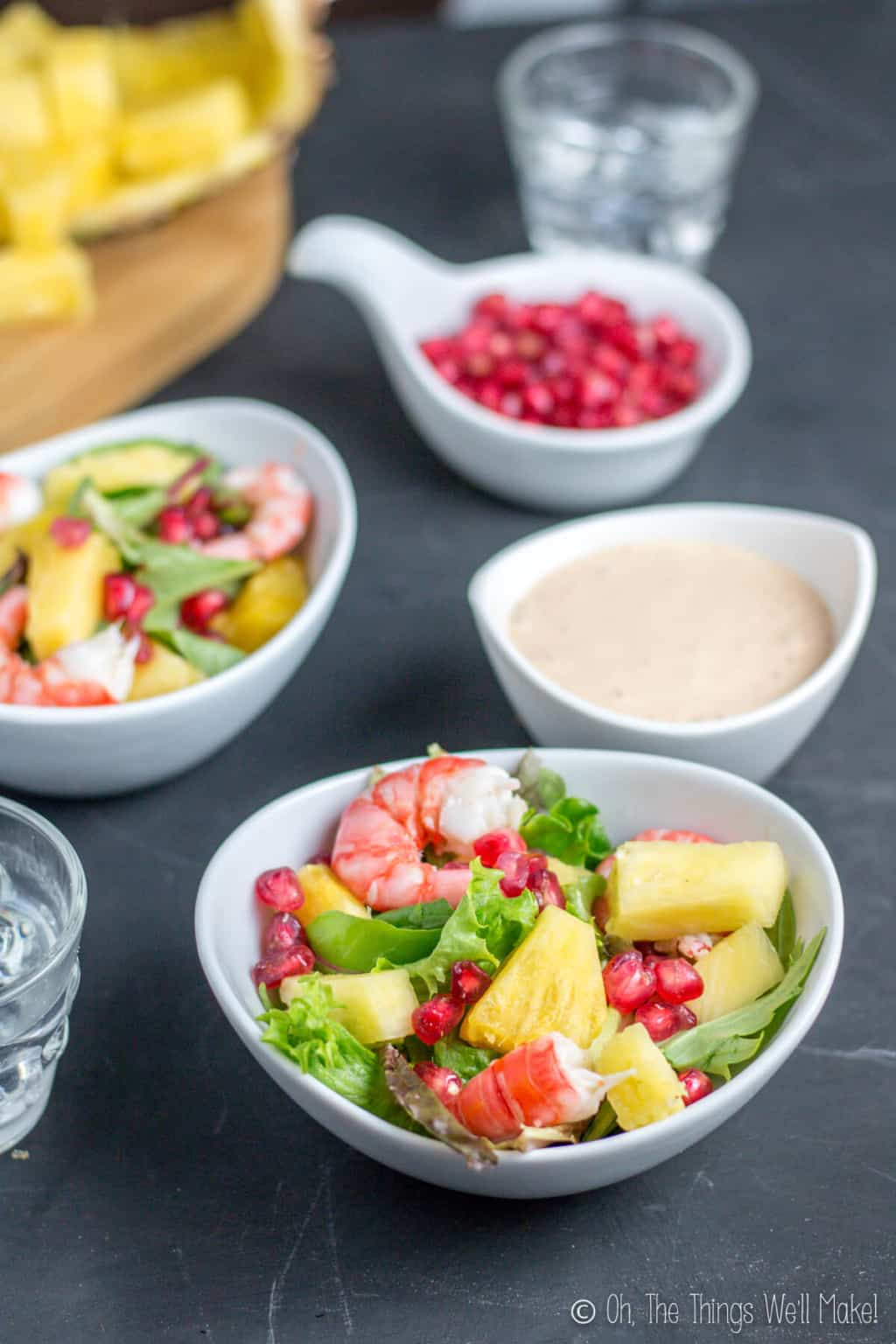 A white bowl of seafood salad in front with a bowl of salsa rosa in the back with another bowl of seafood salad beside it and a bowl of pomegranates at the back.