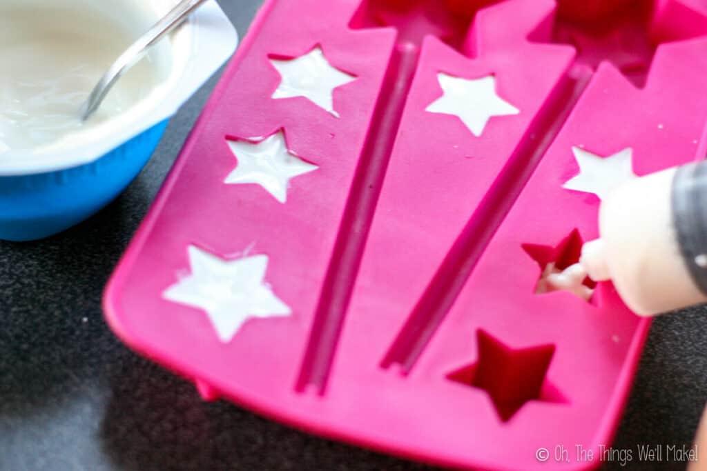 Filling a star-shaped ice cube tray with greek yogurt