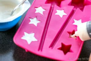 Filling a star-shaped ice cube tray with greek yogurt