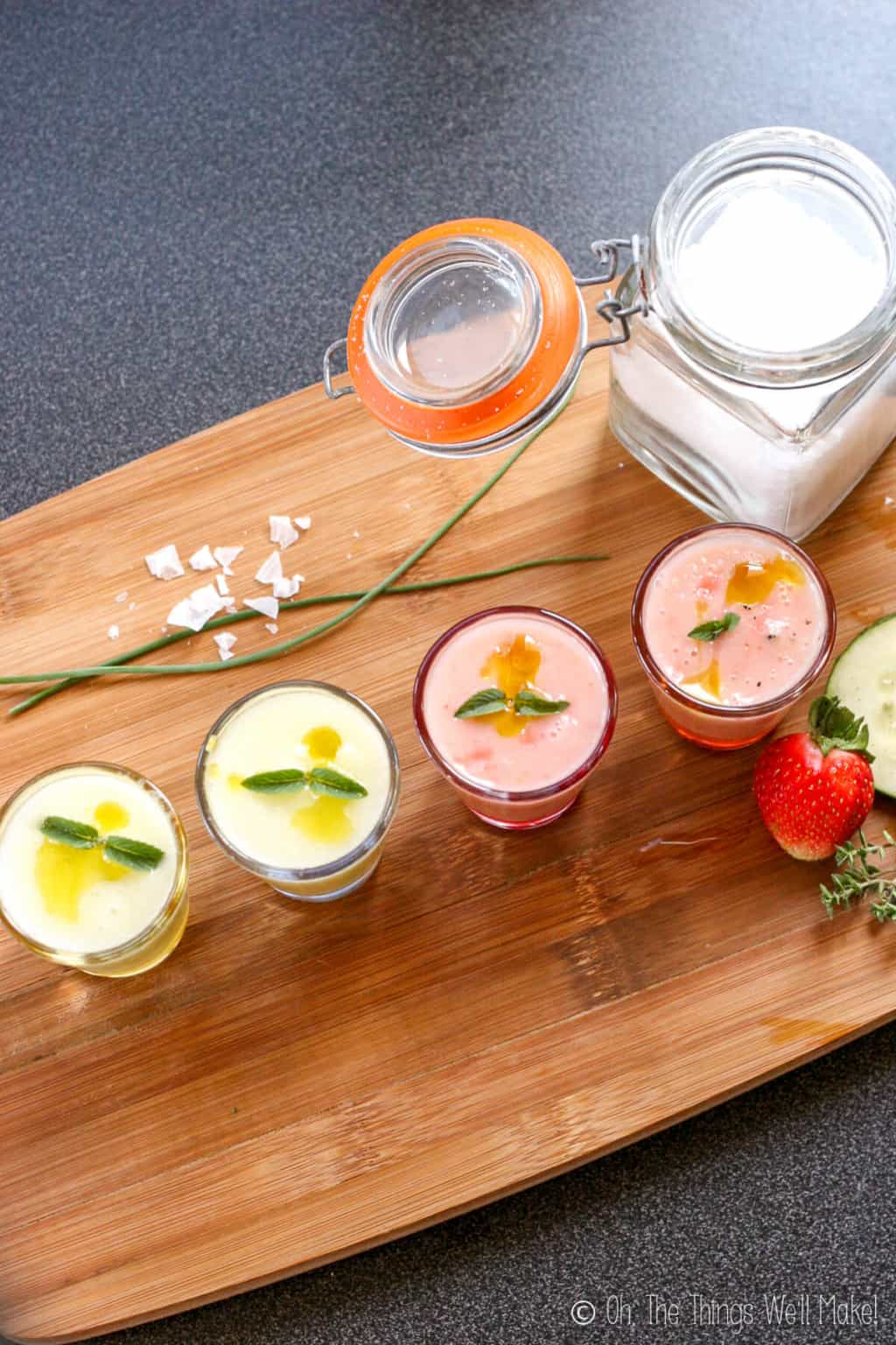 Overhead view of 4 shot glasses filled with a chilled gazpacho soup. The two on the left are green, the two on the right are pink. All are garnished with mint.