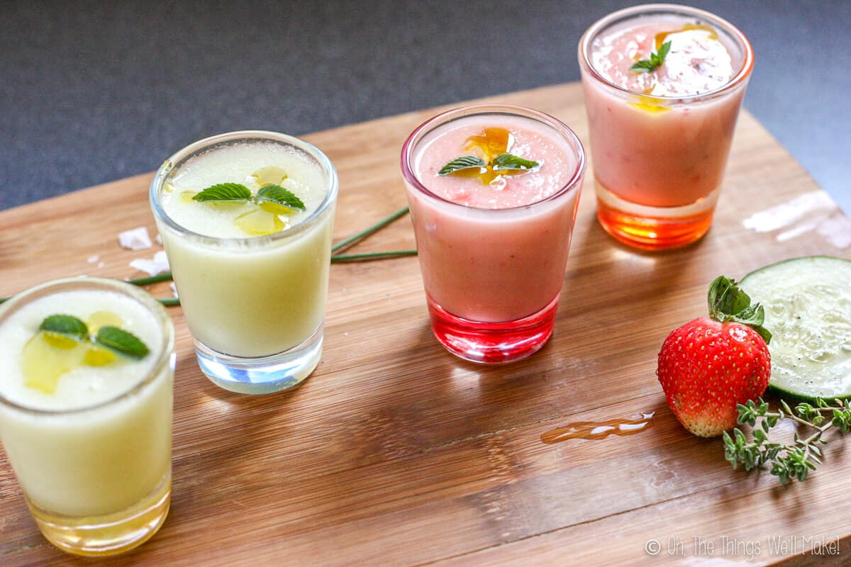 Side view of 4 shot glasses filled with a chilled gazpacho soup. The two on the left are green, the two on the right are pink. All are garnished with mint.