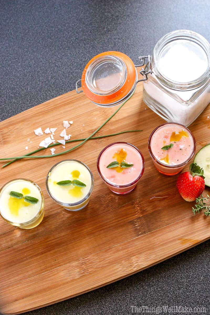 Overhead view of 4 shotglasses filled with a chilled gazpacho soup. The two n the left are green, the tow on the right are pink. All are garnished with mint.