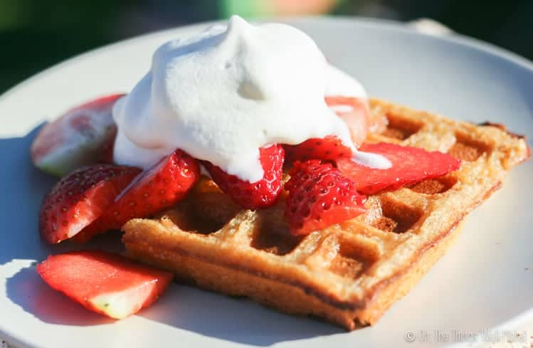 homemade grain free waffles covered with fresh strawberries and homemade whipped cream.