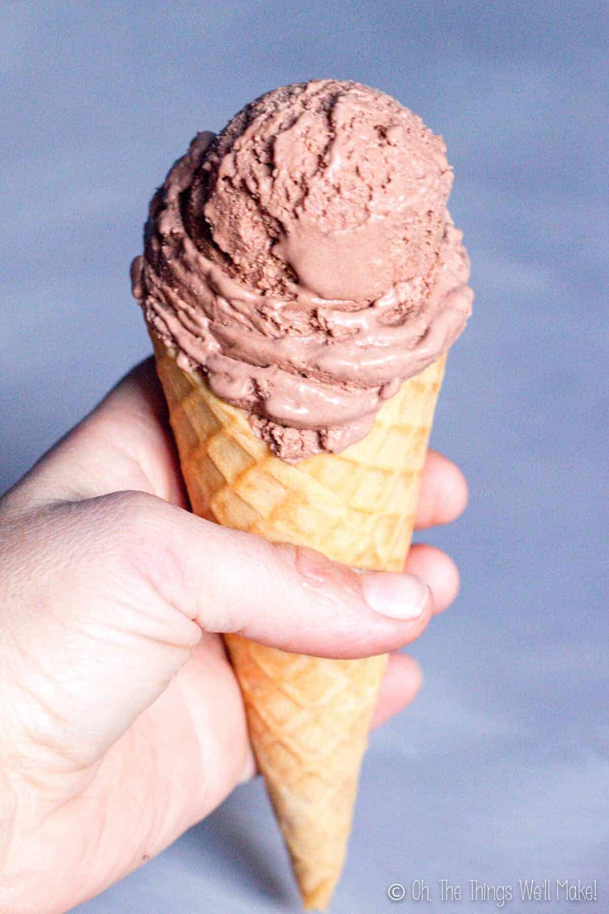 Closeup of a hand holding a chocolate ice cream cone in a homemade waffle cone.