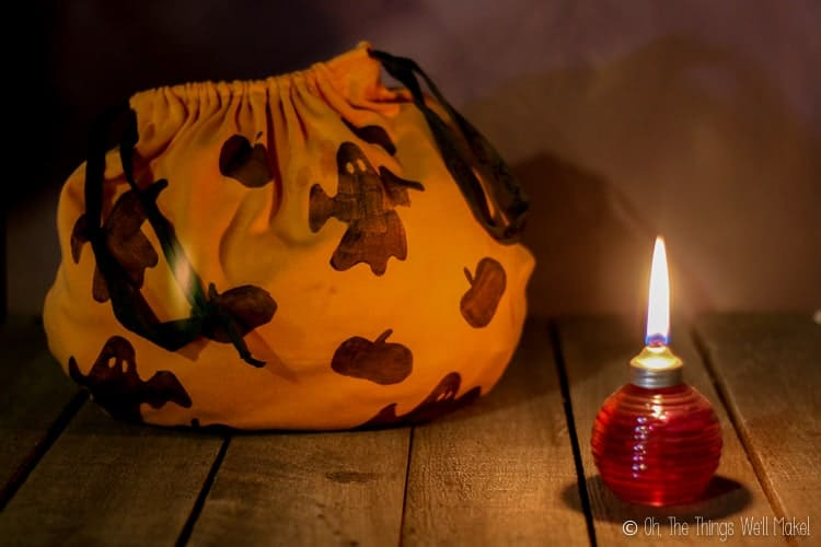 A homemade trick-or-treat bag in the dark being lit by a small oil lamp