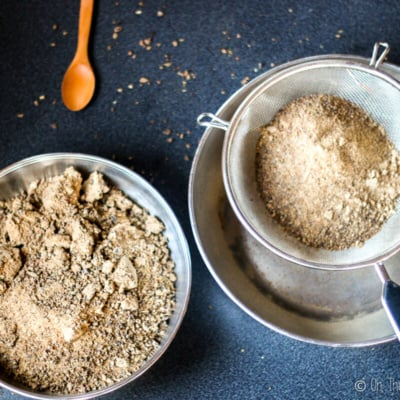 Overhead view of carob flour being sifted with a metal strainer