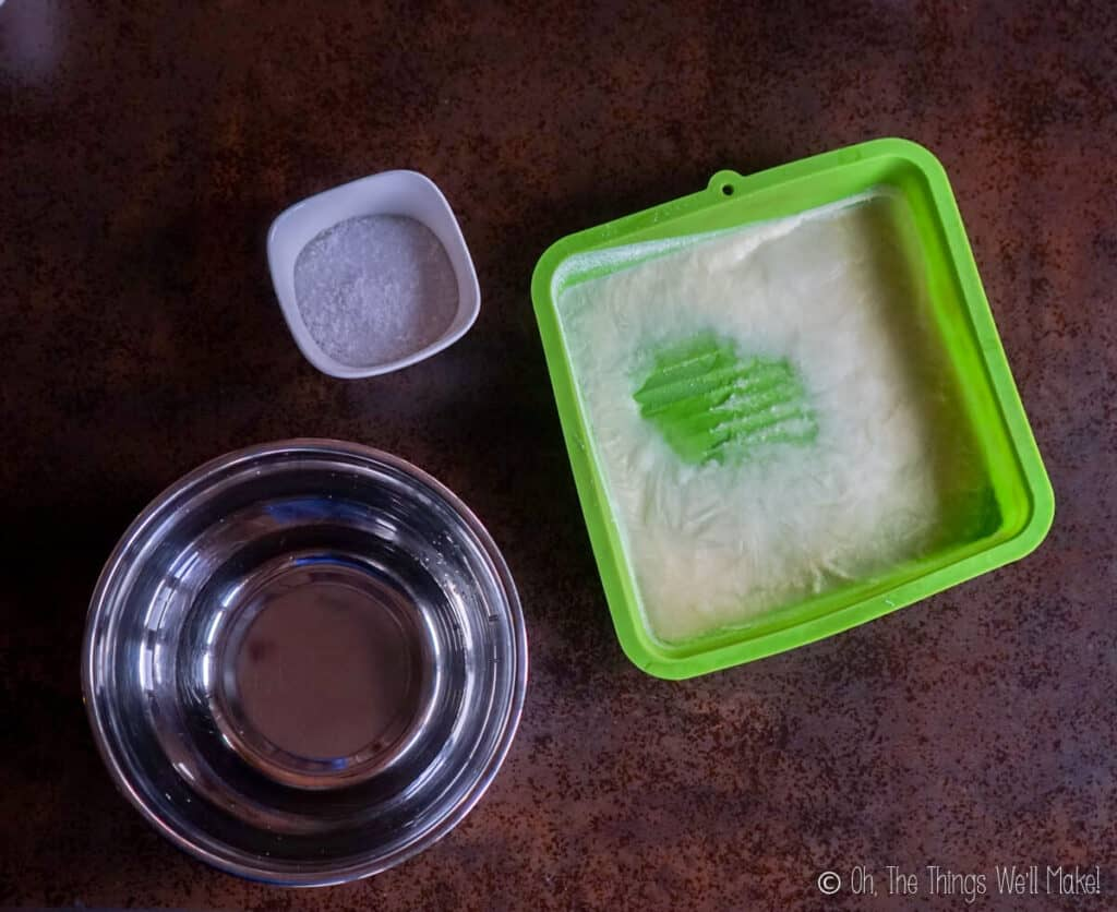 Overhead view of frozen goat milk in a pan, a bowl of lye, and a bowl of water.