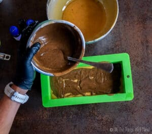 Pouring a dark colored spiced soap mixture into a soap mold over a lighter colored soap mixture