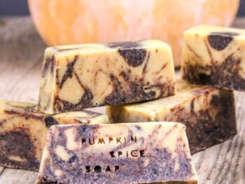 """Closeup of pumpkin spice soap with the words """"pumpkin spice soap"""" pressed into the front bar."""
