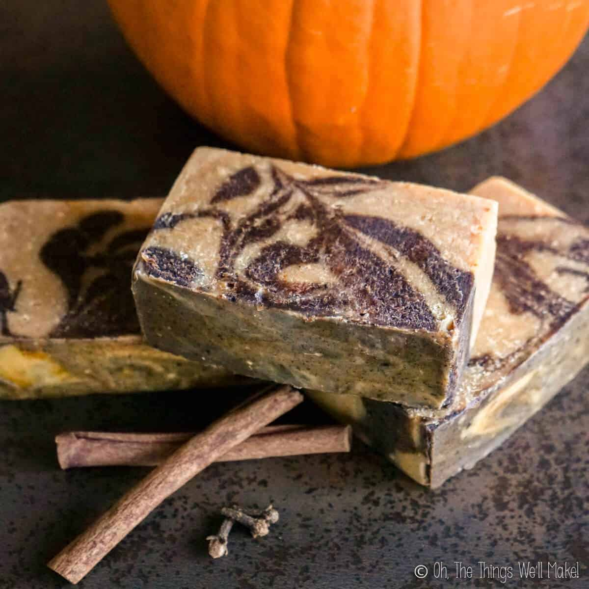 Overhead view of 3 bars of pumpkin spice soap surrounded by dried spices and a pumpkin