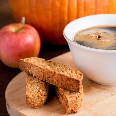 Close-up of three pieces of pumpkin spice biscotti cookies placed beside a cup of coffee on a wooden platter with an apple and pumpkin in the background.