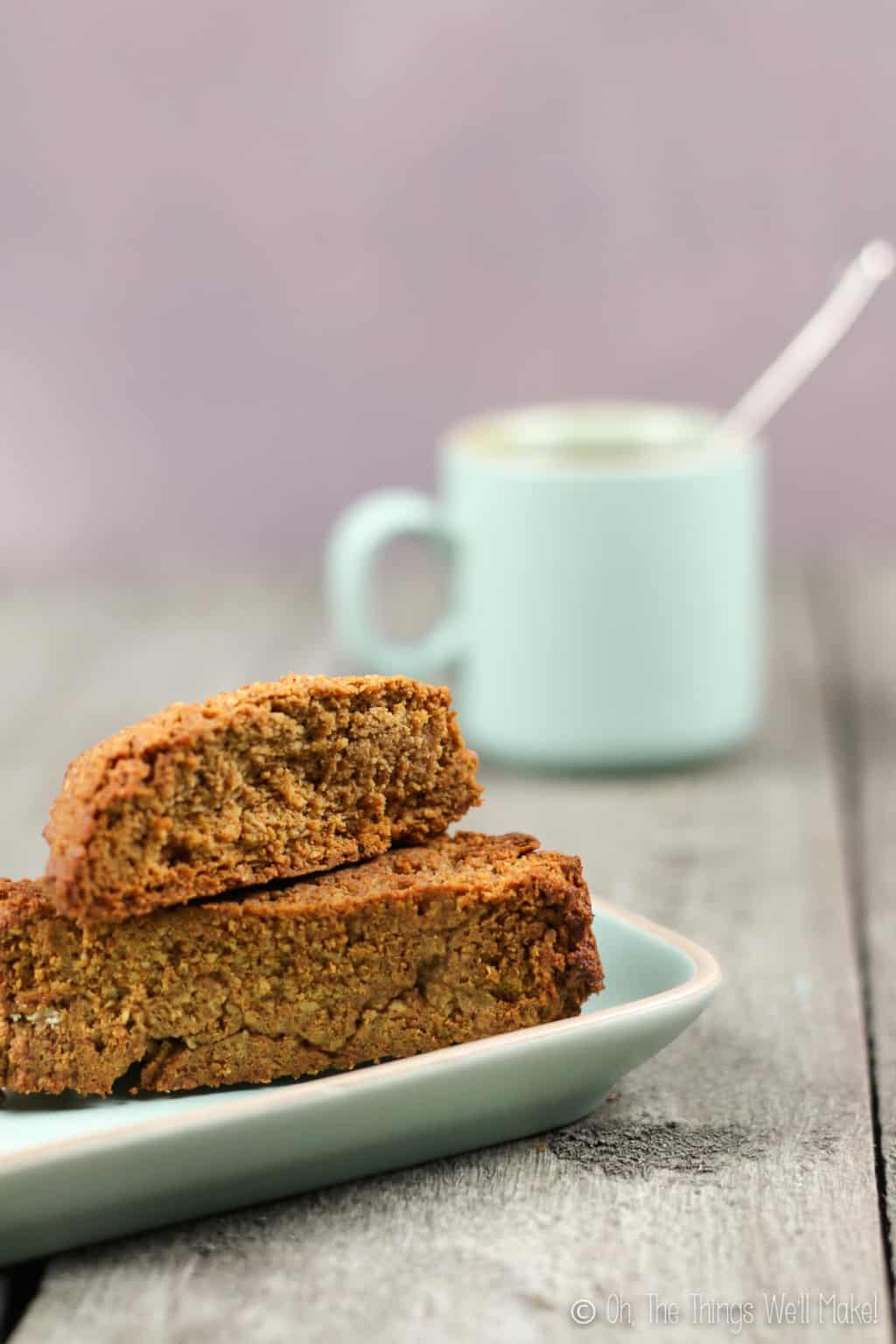 My original pumpkin spice biscotti on a plate in front of a light turquoise cup of coffee.