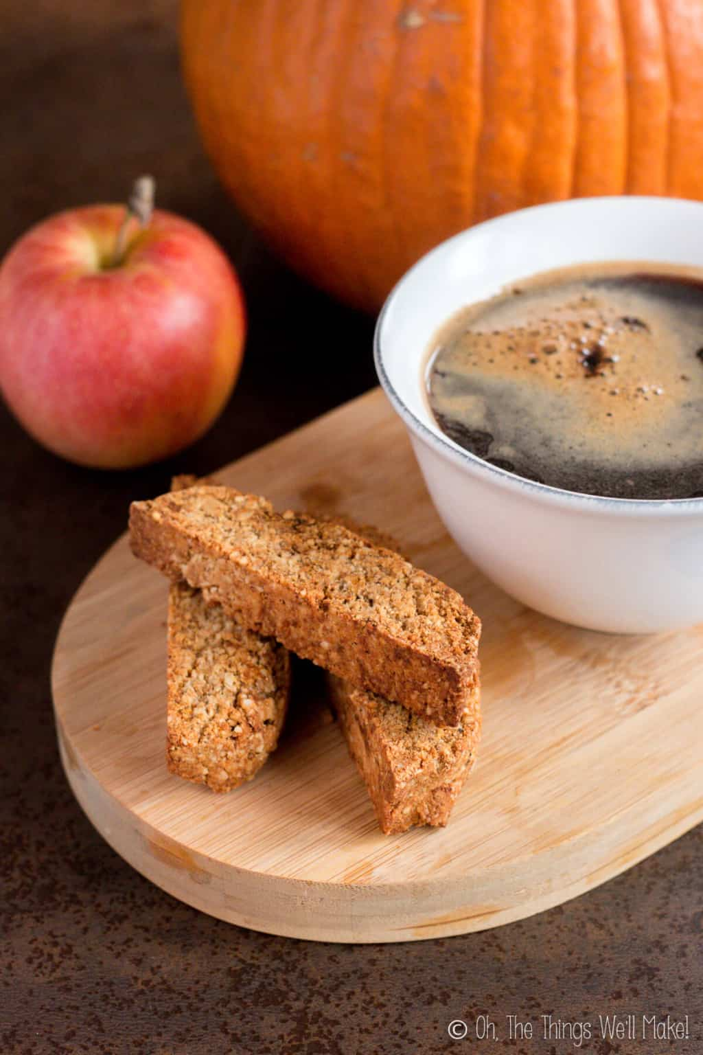 Three pumpkin spice biscotti on a wooden board with a cup of coffee on the side, and an apple in the background.
