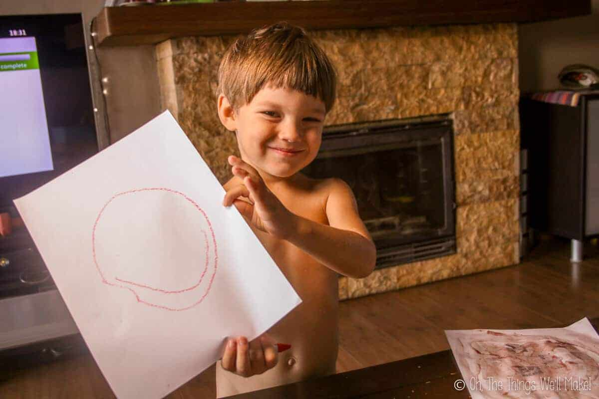 a boy holding a sheet of paper with a smiley face painted on it.