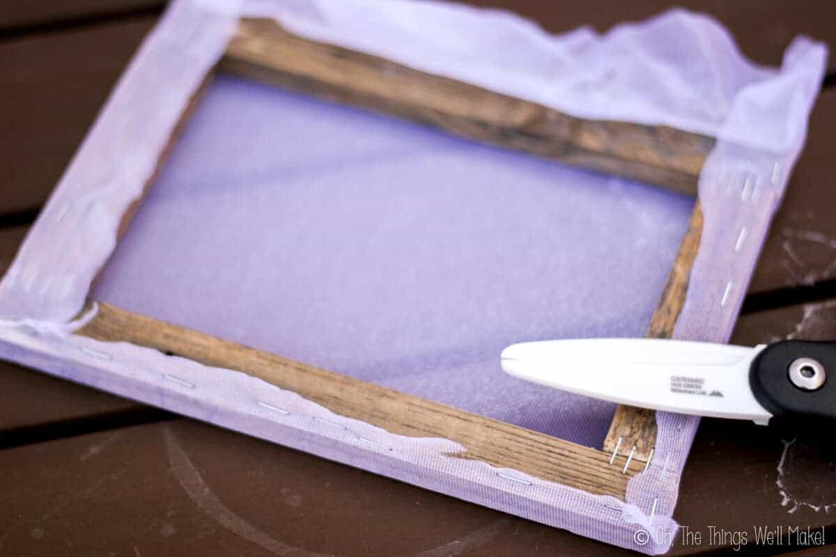 Cutting the excess cloth off a frame prepared for silk screening