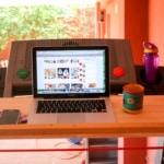 A computer, a phone, and a mug on a removable desk on a treadmill.