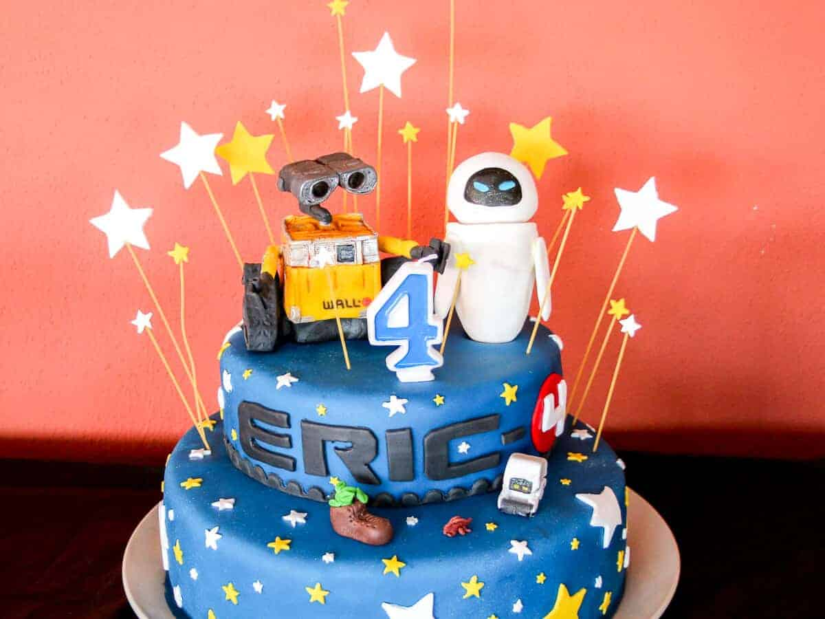 A Star Wars themed two layer birthday cake covered in blue fondant and decorated with white and yellow stars with wall-e and eve on top.