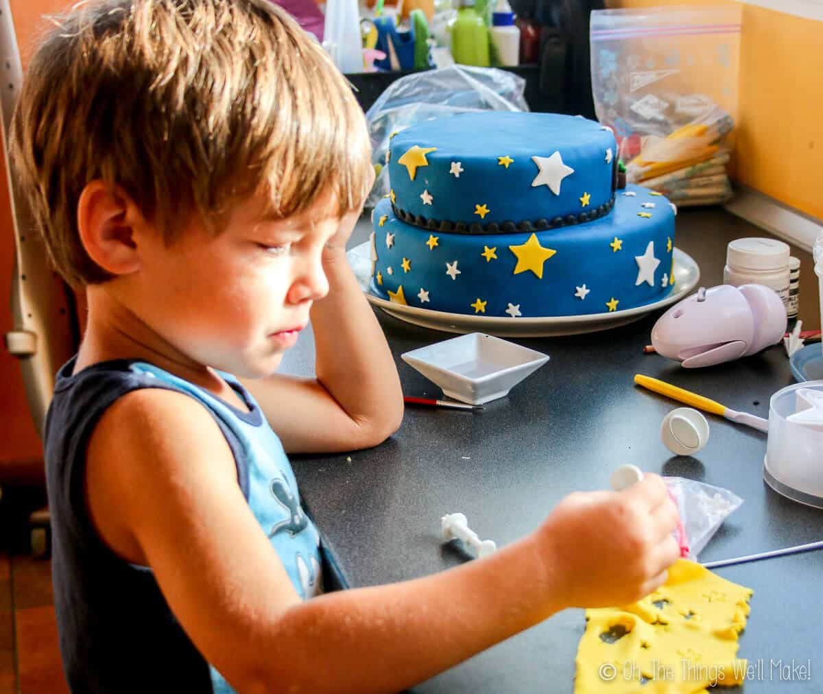 A young boy cutting out stars with a stamp on a piece of yellow fondant.