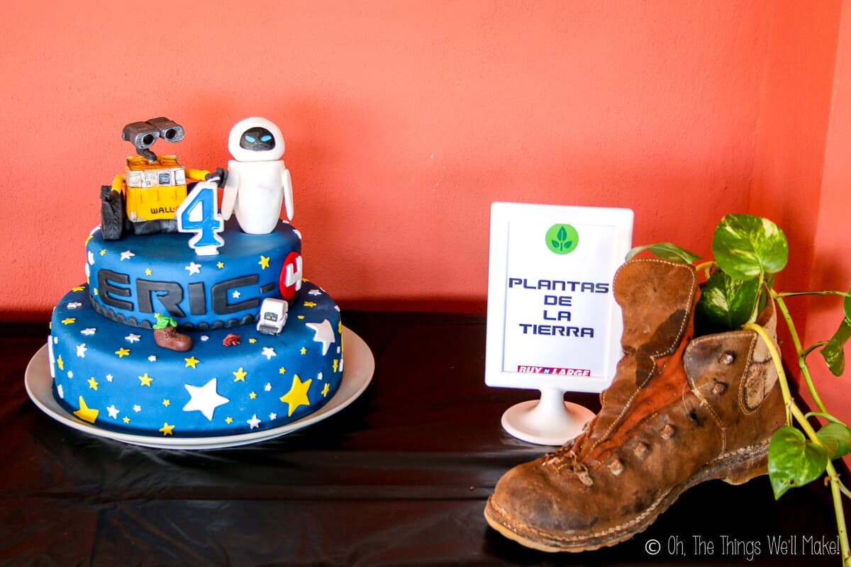 """A table with Wall-E themed cake and decor. On the left is a blue fondant cake decorated with white and yellow stars, Wall-E and Eve fondant decor on top, and a number four candle. On the right is a brown boot with a plant vine tucked in it and a picture frame beside it saying """"plantas de la tierra."""""""