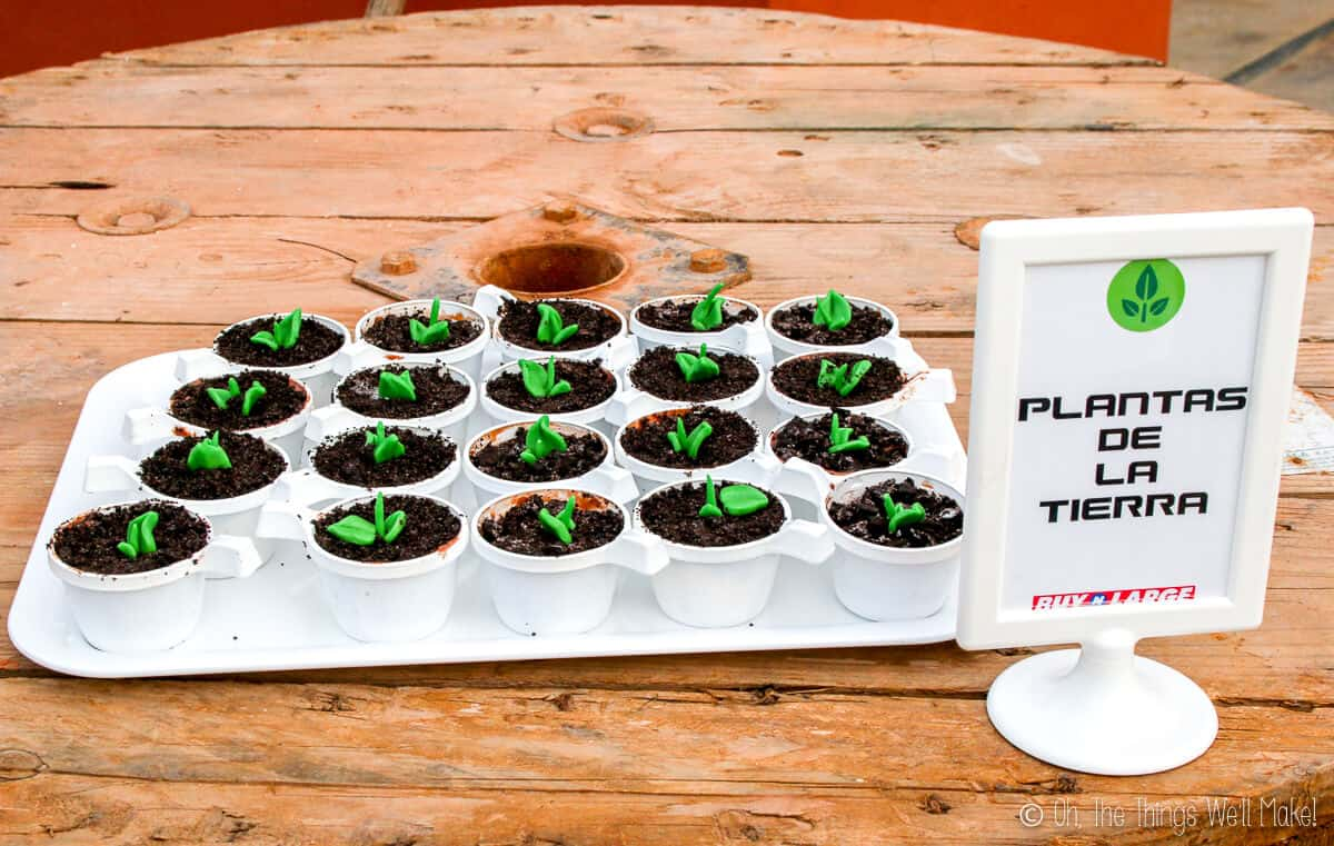 """A tray full of handmade plants dessert which is crushed oreo placed on top of cups full of ice cream with a picture frame on the side saying """"plantas de la terra."""""""