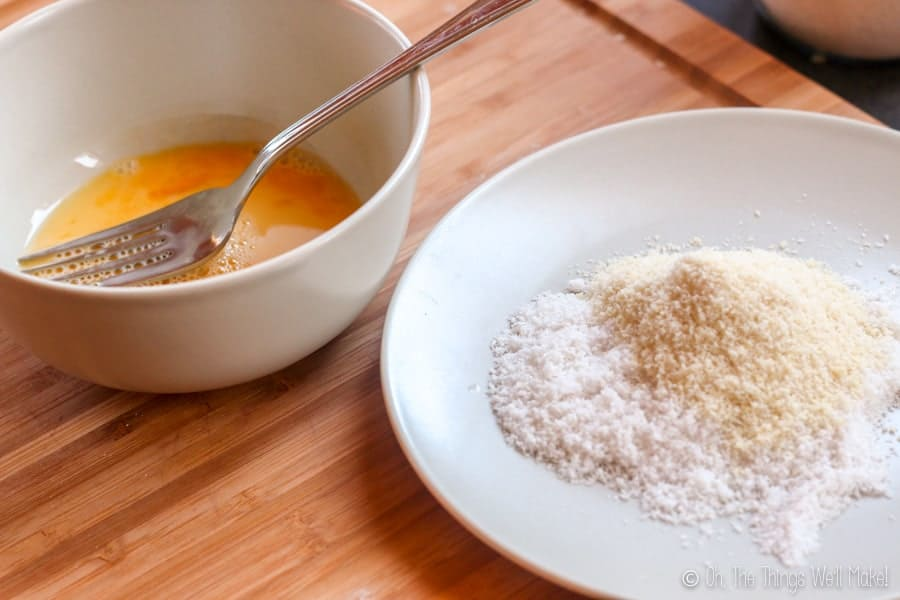 A bowl of beaten egg in a bowl next to a plate with a flour mixture