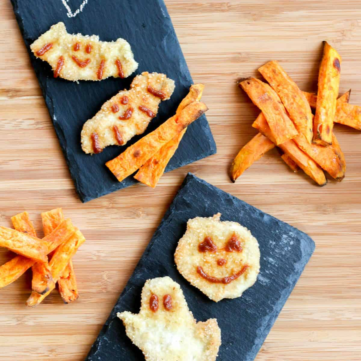 Halloween chicken nuggets shaped like ghosts, pumpkins, and bats, decorated with BBQ sauce and served with sweet potato fries.