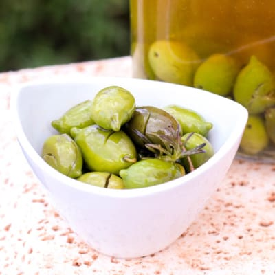 A bowl full of homemade salt cured green olives with a jar full of olives in a liquid mixture of water, extra virgin olive oil, and herbs.
